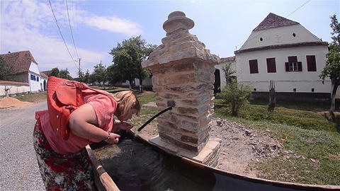 Woman Drink Water From A Spring Arranged On The Main Street Of The Small Village stock footage