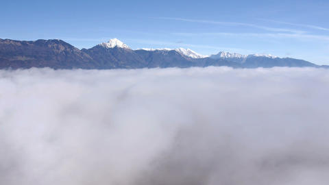 Aerial - Descending through the mist. Majestic moutains above the clouds Footage