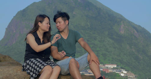 Young Asian couple sitting in beautiful location relaxed on rocks near ocean Footage
