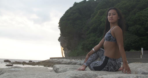 Tanned Asian Japanese Girl Doing Yoga On Rocks Beach Side 4K stock footage