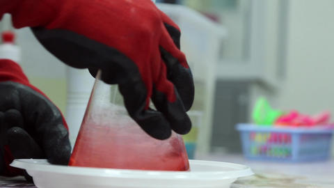 A Lab Technician Mixes A Pink Liquid In The Flask stock footage