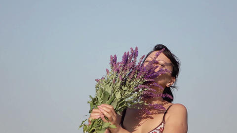 Woman Smelling A Bouquet Of Wildflowers stock footage