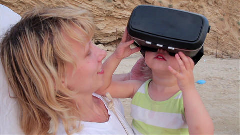 Little girl on mother's hands with glasses of virtual reality Footage