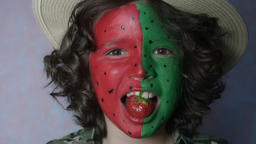 4k Shot Of A Cute Child Posing With Coloured Face And A Strawberry stock footage