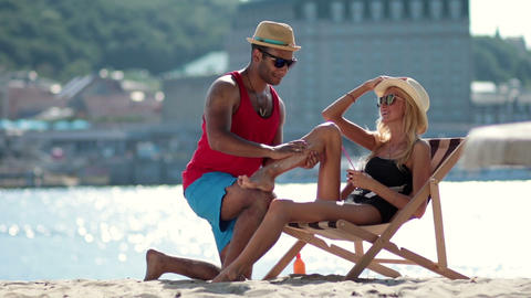 Man Applying Sunscreen On Girlfriends Leg On Beach stock footage