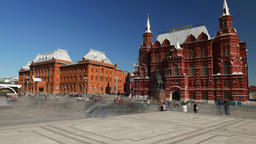 People rush across square, red building of State Historical Museum, time lapse Footage