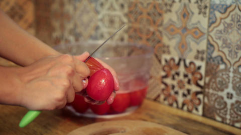 Female Hands Peeling Boiled Tomatoes In Kitchen stock footage