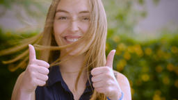 Portrait of an attractive young woman with long blond hair smiling and giving th Footage