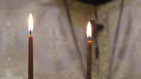 Two yellow candle burning on the altar in the church in front of priest 98 Footage