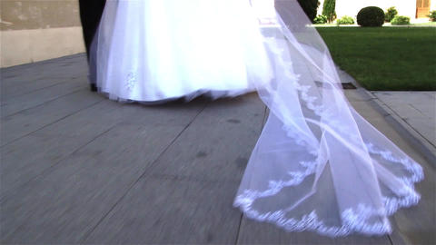 Bridal veil dragged on the concrete driveway behind the woman dressed in white 0 Footage