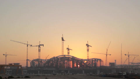 The rising sun appears from behind a silhouette building of the construction sit Footage