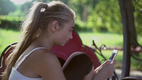 Beautiful Blonde Girl Sitting On A Bench In The Park, Smiling And Review Mobile  stock footage