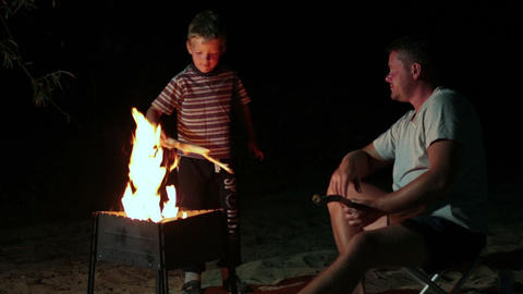 Family have a rest in camp at night near campfire Footage