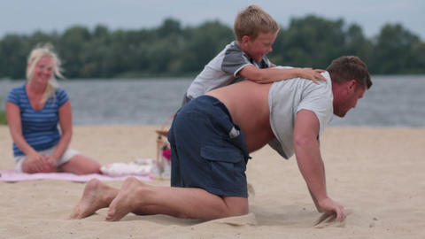 Father giving his son piggyback ride at the beach Footage