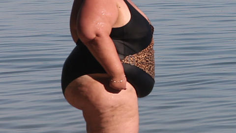 Women with overweight standing in a swimsuit at the water surface ビデオ