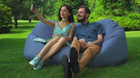 A young girl and a guy sitting in a chair and make selfie phone Footage
