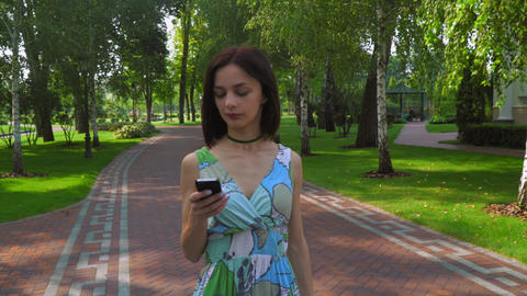 A Young Girl Goes On A Path In The Park And Gaining A Message On The Phone stock footage