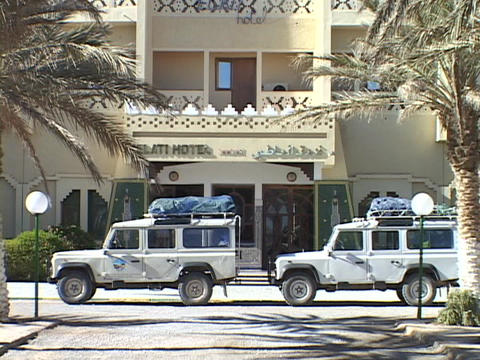 Land Rovers Sit Parked In Front Of A Hotel Prepared For A Safari stock footage