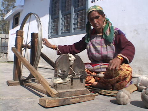 An old woman spins yarn onto a wheel Footage