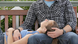 Young lovers in 20s show affection and romance cuddle on park bench in garden Footage