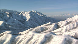 Aerial shot of snowy mountains with salt lake valley in the distance Footage