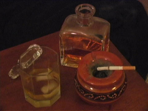 A Cigarette Burns In An Ashtray With Ice Melting In A Glass Next To A Bar Bottle Of Liquor stock footage