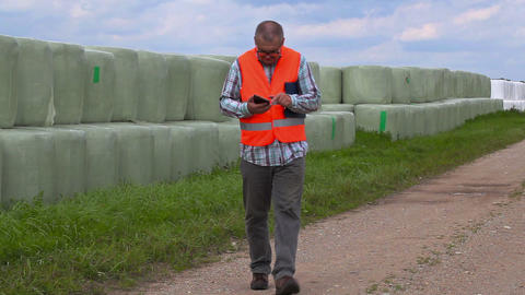 Farmer using smart phone on the rural road near hay bales Footage