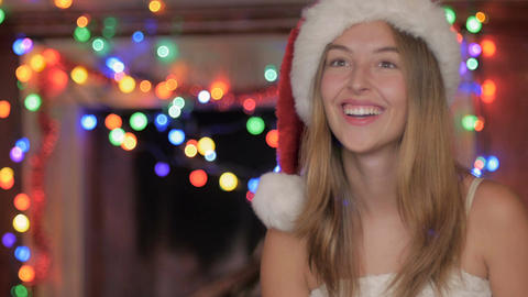 A jolly happy attractive blond woman wearing a red Santa hat laughing in the hol Footage