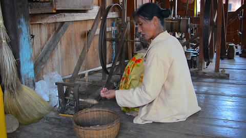 Woman spin yarn thread on traditional wooden distaff spinning wheel Footage
