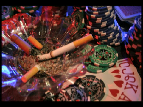 Time-lapse of a cigarette burning in an ashtray surrounded by poker chips and playing cards Footage