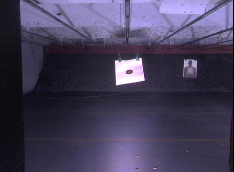 A Target At An Indoor Shooting Range Recedes Toward A Far Wall stock footage