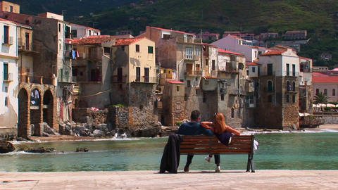 A Couple Sits On A Bench Overlooking The Ocean And Houses In Cefalu, Italy stock footage