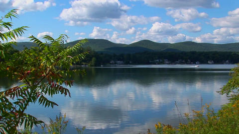 A Glassy Rural Lake In Central Vermont Is Surrounded By Trees And A Cloudy Blue Sky stock footage
