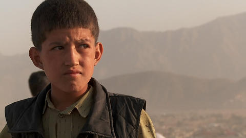 Close Up Portrait Of Boy's Face As Friends Fly Kites In An Empty Lot In Kabul, Afghanistan stock footage