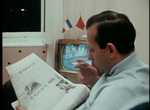 A dated shot of a man reading a newspaper, smoking a cigarette and watching TV Footage