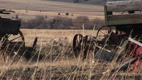 Broken and abandoned farm machinery rest in a field that overlooks the dry prairie beyond Footage