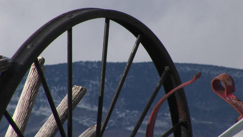 Camera looks at mountains through the spokes of abandoned wagon wheels Footage