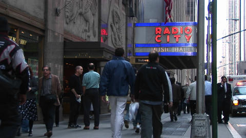 Medium-shot of people walking under the Radio City Music Hall marquee in New York City, New York Footage