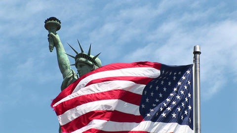 The American Flag Waves In The Foreground With The Statue Of Liberty Standing Proudly Behind stock footage