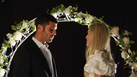 Bride And Groom Laughing Under A Flower Arch stock footage