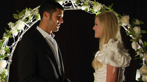 Bride And Groom Stand Under An Arch Of Flowers As The Man Slips A Ring On The Woman's Finger stock footage