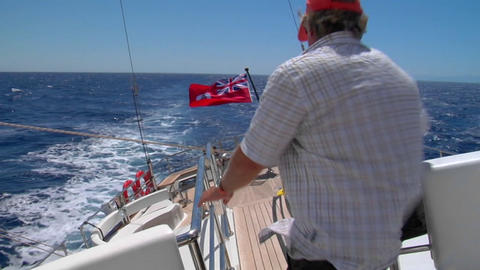 A View Of The Aft Deck Of A Sailboat Healing Starboard, A Man Crosses The Frame Down To The Aft Deck stock footage