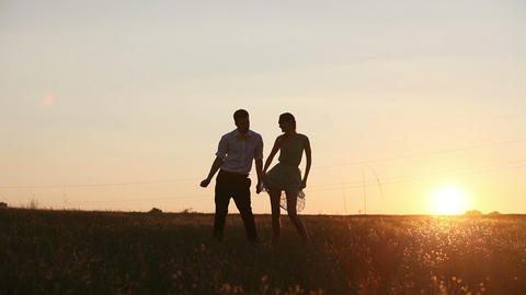 Young Couple Silhouettes Dancing On The Field At Sunset stock footage