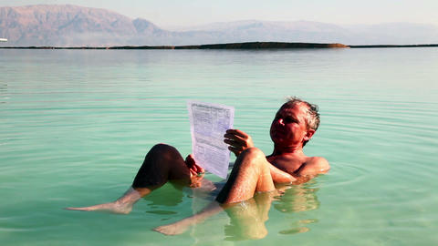 Man reads a relaxed lying in Dead Sea water Footage