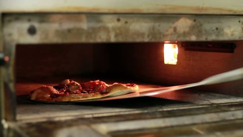 Cook Pulls A Pizza Out Of The Oven stock footage