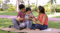 Young Asian Family Teaching Son To Read In Park - Dolly Reveal stock footage