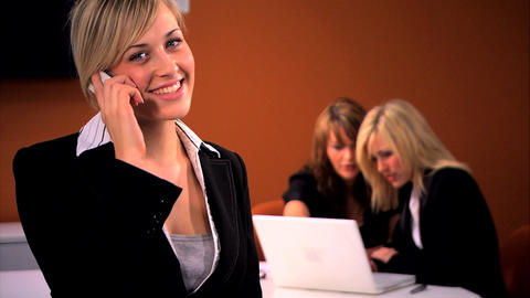 Beautiful Blonde Businesswoman Chats On The Cell With Her Colleagues In Background stock footage