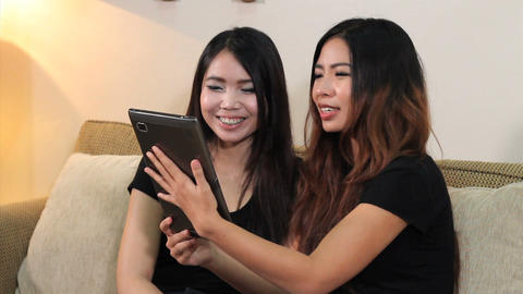 Asian Women Talk To Friends On PC Tablet stock footage