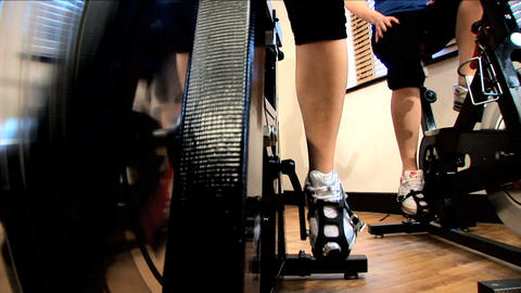 Close-up legs & feet working an exercise machine at a gym Footage