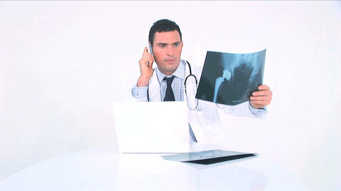 Doctor Examining X-ray And Consulting It On The Phone stock footage